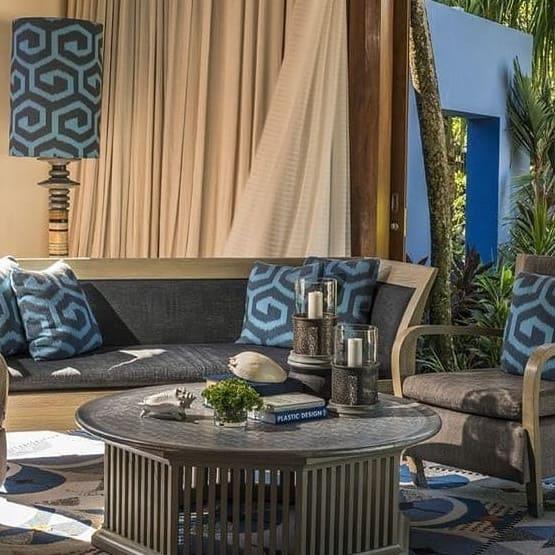 Showroom in Thailand mit hellen Farben. Beige Vorhänge mit grauen Möbeln und blauen Kissen.